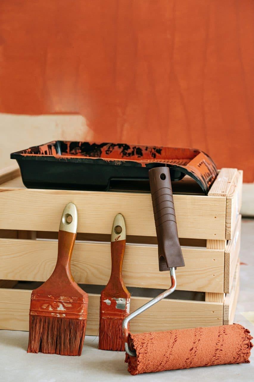 bac à peinture , rouleaux, pinceaux sur une boite en bois